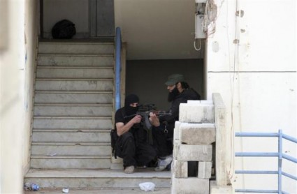 Sunni Muslim fighters stand with their weapons inside a building inTripoli, northern Lebanon